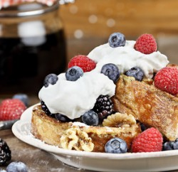 Delicious golden french toast with fresh blackberries, raspberries, blueberries, powdered sugar and whipped cream. Extreme shallow depth of field.