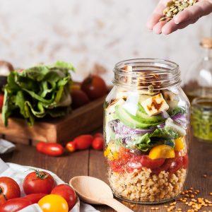 Une salade mélangée avec des graines et du tofu dans un bocal en verre