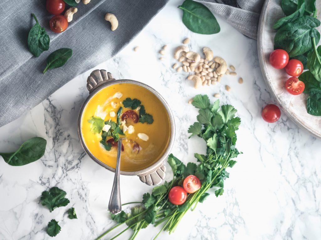 Soupe bio dans un bol et ingrédients sur le comptoir