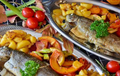 Plat de poisson cuisiné avc des pommes de terre, des aromates et des fruits