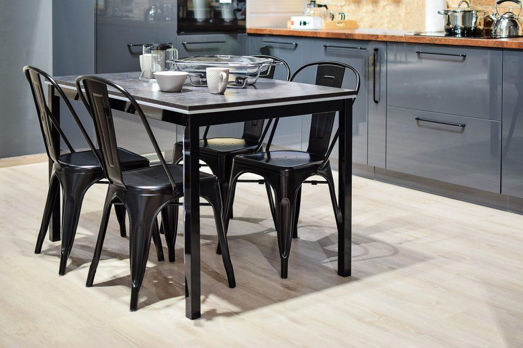 cuisine avec tables et chaises au milieu et vaisselle posée sur la table
